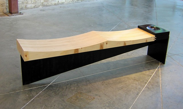 Contemporary bench built with baltic birch, wenge, and steel. The seat is sculpted with two gentle waves, and the end of the seat has a wenge block with a shallow bowl carved into it. The wood seat rests on a steel bench base. This is one of our signature designs.