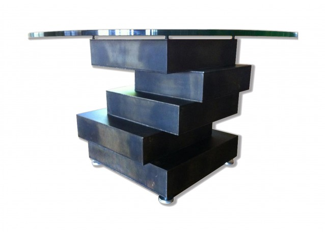 Contemporary table built with stacked steel volumes that support a glass tabletop. There are five steel volumes stacked on top of each other, and they are stacked off-kilter and welded together, to form a provocative table base. The steel has a mottled black patina with a commercial-grade clearcoat. And the table also features load-rated levelers for uneven surfaces.
