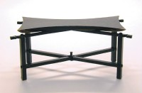 Contemporary table built with wenge and forged steel. The wenge tabletop is shaped like a japanese butterfly. The steel base has traditional blacksmith details, including hammered texture and twisted steel.