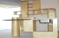 Contemporary kitchen cabinets built out of natural baltic birch with a custom stainless steel countertop. Features notched cabinet door pulls, curved drawers, and custom installation in northern New Mexico. Designed by Steven Holl Architects for the artist Richard Tuttle.