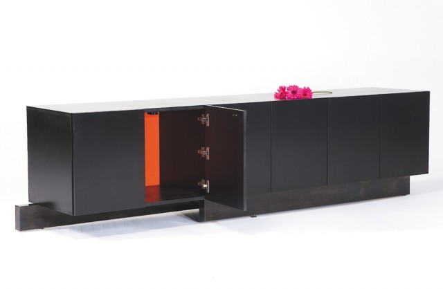 Contemporary credenza built with lacquered wood and steel. The credenza has a series of touch-latch doors. The outside of the credenza is black. The cabinet back on the inside of the credenza is rose red, and this creates an explosion of color from the inside when you open the doors. The credenza is supported by a u-shaped steel plinth with a black patina.