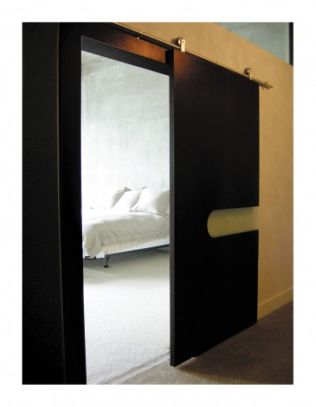Contemporary sliding door built with wenge veneer and sandblasted glass. The sliding door hardware is solid stainless steel from Germany. The door is slab-style but dimensionally stable, since it's built with veneer. A cut-out in the door features an inset of sandblasted glass.