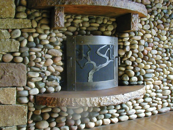 Forged fireplace screen that features a single, sexy live oak tree detail. Handles on either side of the curved fireplace screen allow it to be moved to one side. People love this fireplace screen.