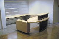 Contemporary reception desk built with white maple and steel. The desk feaures a transaction top, an oval desktop, several file drawers, and additional work space behind the desk. The maple is natural with a commercial-grade protective finish, and the steel has a custom black patina.