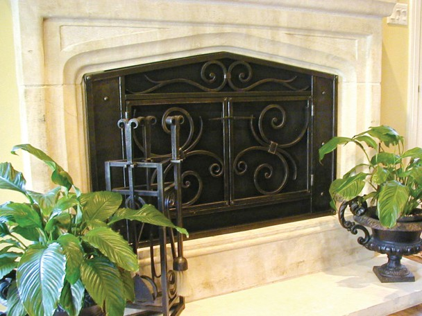 Fireplace screen built with forged steel. Features forged scrolls and hammered texture and double doors and a custom door latch. Very traditional design but very custom by Ironwood Industries.