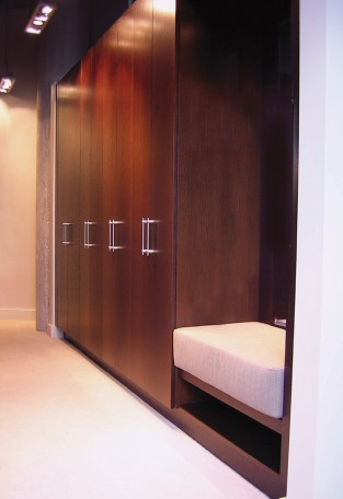 Contemporary closet built with wenge veneer. Features full-length cabinet doors and a built-in cushioned seat.
