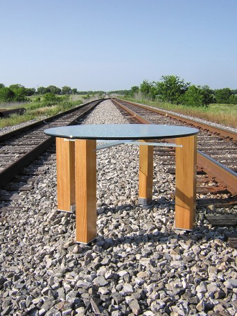 Contemporary table with round glass top, antique longleaf pine legs, and aluminum stretchers that connect the legs. The aluminum fits into the longleaf pine legs with provocative joinery. The longleaf pine has a natural finish. The table is photographed on the railroad tracks outside our studio in Texas.