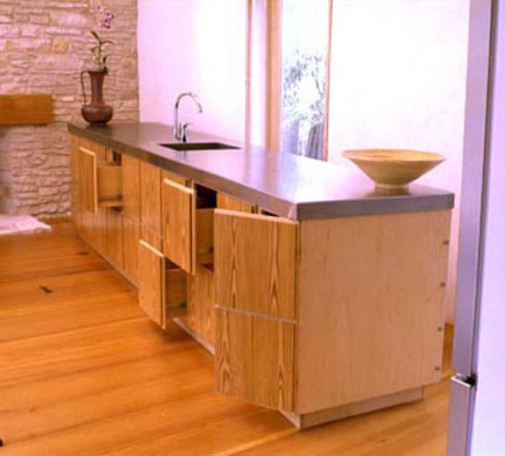 Contemporary kitchen island with several cabinet doors and drawers open