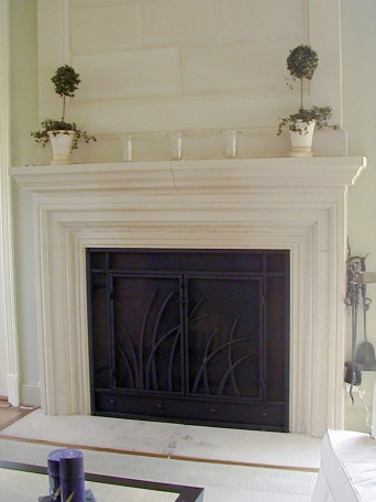 Fireplace screen built with forged steel. Features fountain grass detail, double doors, and custom door latch.